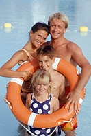 Parents with children (8-9) (6-7) in pool with lifebelt, portrait