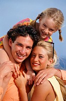Parents with daughter (8-9) embracing at seaside, portrait