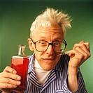 Senior man taking spoonful of tonic, (Portrait)