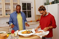 Gay couple preparing food in kitchen