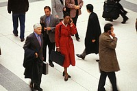 Business people walking in busy station, elevated view
