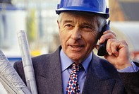 Architect in hardhat talking on mobile phone, (Close-up)