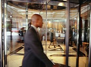 Businessman walking through revolving door of office, side view