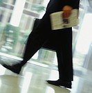 Businessman walking in building (low section)