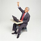 Businessman sitting at school desk, raising hand