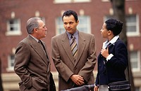 Three business people talking in street