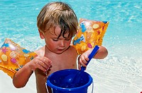 Boy with spade and bucket at swimming pool