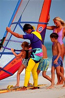 Family with windsurfing board on beach