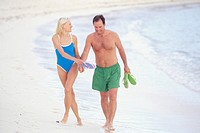 Couple walking together on beach, holding sandals