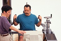 Man receiving physical therapy at gym