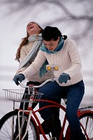 Two teenage girls (14-17) riding bicycle