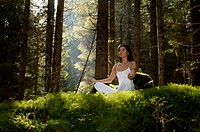 Woman meditating in forest, looking away, low angle view