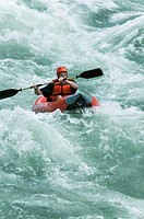 lifestyle shot of a young adult male as he rides a kayak down some river rapids