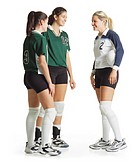 two young caucasian female volleyball teammates in green jerseys chat with a third female caucasian volleyball player from an opposing team