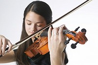 portrait of an asian female teen in a black dress as she plays her violin