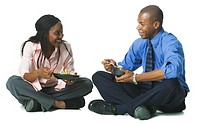 two african american business colleagues sit and eat lunch together