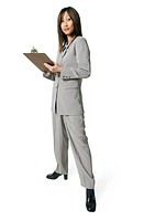 an adult asian busniess woman in a grey outfit looks over information on a clipboard