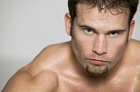 fitness portrait of a muscular shirtless male as he glares at the camera