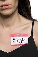 conceptual shot of an adult woman with a name tag that states she is single