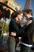 medium shot of a young adult couple as they embrace near a carousel in paris