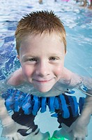 lifestyle portrait of a male child as he plays in a swimming pool