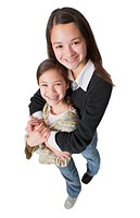 an asian teenage girl in jeans and a black sweater wraps her arms around her little sister and smiles up into the camera