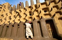 Man plastering mosque with mud, Dogon Valley, Mali,