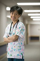 lifestyle shot of an adult female doctor in a hospital hallway as she folds her arms and smiles