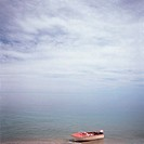 a red and white beached fishing boat sits on the sand of a blue ocean with blue sky and clouds rising above it