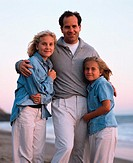 father and two daughters stand together on the beach