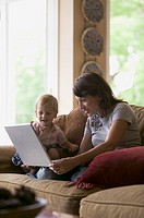 lifestyle shot of a mother sitting on a couch with her child as she uses a computer