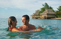 a caucasian couple embrace in water at a tropical resort