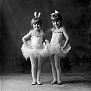 Two young caucasian sisters pose in their ballet costumes ready to dance