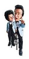a caucasian elvis look alike acts as a ventriloquist while wearing a powder blue tuxedo jacket and ruffled shirt with black tuxedo pants and holding a...