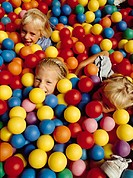 Three caucasian blonde girls giggle in a bunch of bright coloured balls