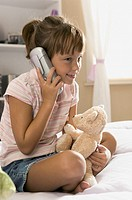 lifestyle portrait of a female child in a pink striped shirt as she chats on the phone