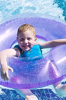 lifestyle portrait of a male child as he floats in a swimming pool with a purple tube