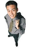 an asian business man holds his jacket over his shoulder and smiles up at the camera