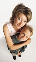 caucasian woman in pink shirt with brown hair stands with arms around preteen blonde son