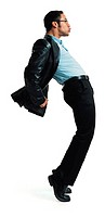 a young latin male modern dancer in glasses and black leather jacket hops up on his toes and thrusts his pelvis foeward