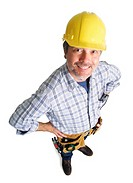 a caucasian male construction worker wearing a tool belt smiles as he looks up at the camera