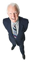 Birdseye view of an elderly caucasian man in a suit grinning at the camera.