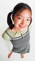 a cute asian girl in ponytails and braces wears a gray jumper and stands barefooted looking up into the camera