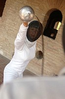 A female fencer in action wearing a fencing mask