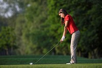 Side view of a teenage girl playing a golf shot