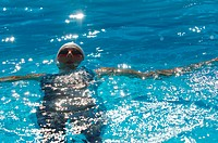 Front View of Female Swimmer Swimming Backstroke