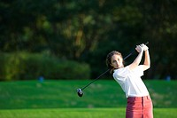 A young woman makes a stroke with a golf club