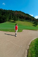 Woman walking towards her golf ball in a bunker