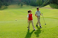 Couple walking down the fairway with their clubs
