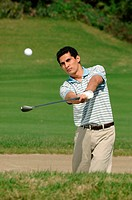 Front view of a man playing a bunker shot
